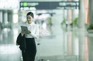 商务女士手提拉杆箱从机场大厅经过并手看ipad图片