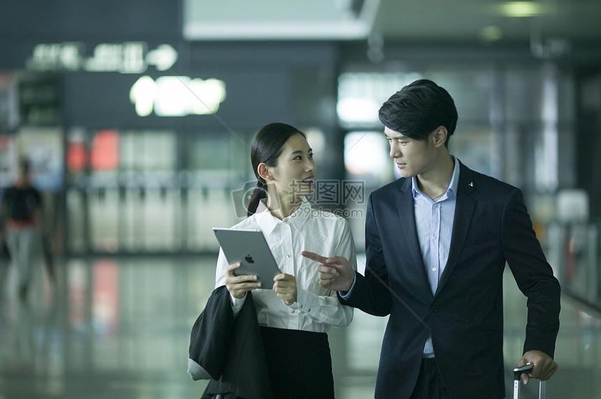 商务男士和女士在经过机场通道里看ipad讨论商业图片