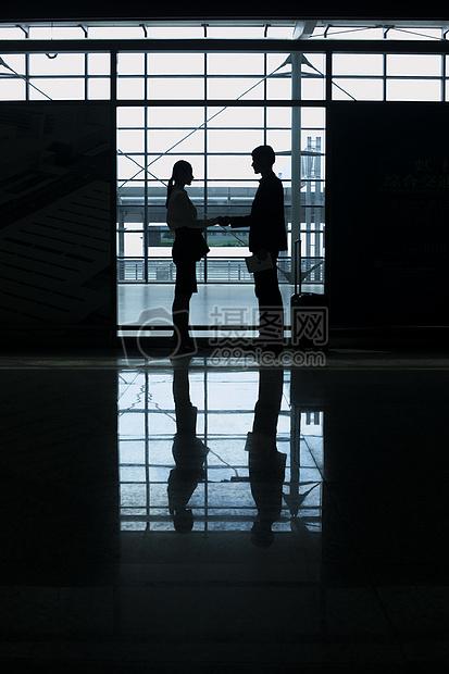 商务男士女士在机场见面会晤握手图片