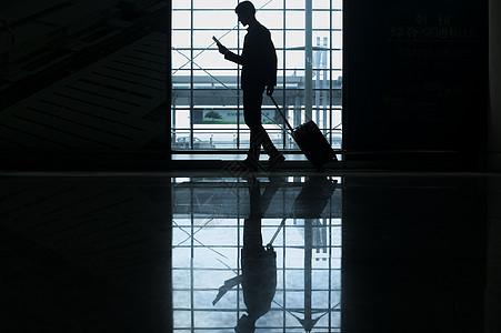 商务男士手提拉杆箱经过机场一边看着手机图片
