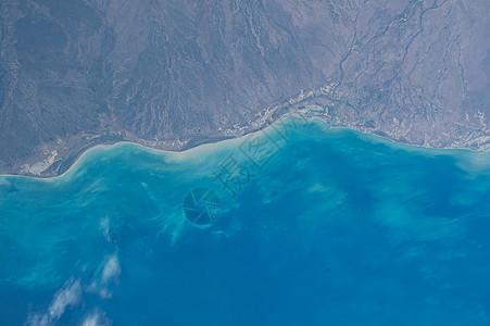 航拍的陆地和海洋湛蓝深邃海岸线图片