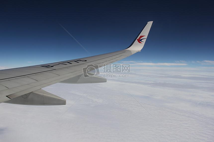 蓝天上飞翔的飞机机翼图片