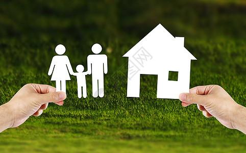 手持有房子和家人在绿色的田野图片