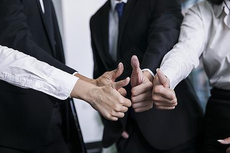 商务团队竖起拇指表达合作成功的信念图片