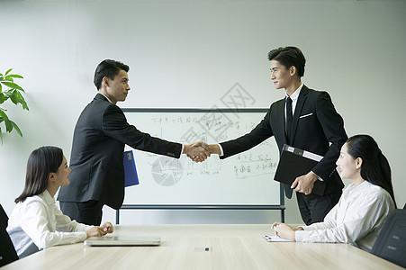 会议室内双方握手达到合作意向图片