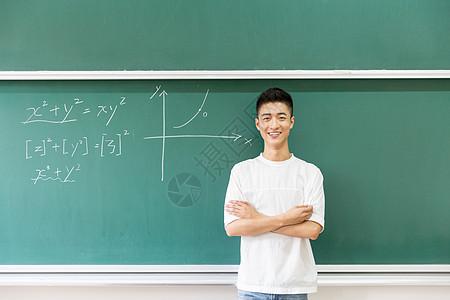 站在大黑板前思考的男生老师图片