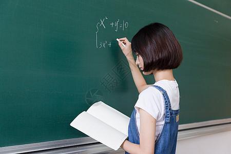正在教室黑板写板书的女生图片
