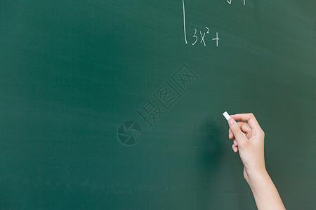 拿着粉笔在黑板上写字的手图片