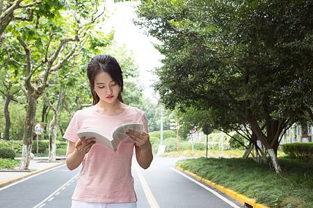拿着书站在校园林荫道上的高中生图片