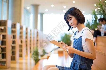 坐在图书馆使用平板的女生图片