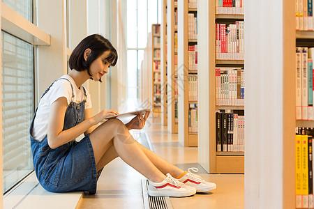 坐在图书馆书架旁看书的可爱女生图片