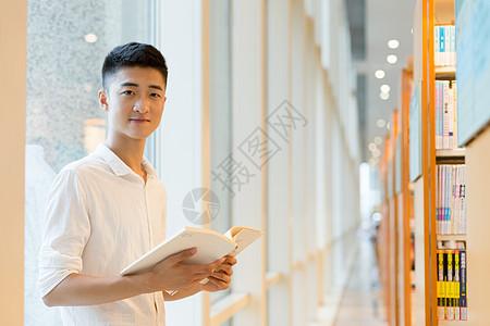 站在图书馆书架旁看书的帅气男高中生同学图片