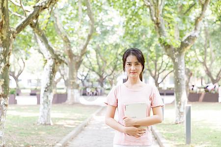 拿着书站在校园林荫道上的女生图片