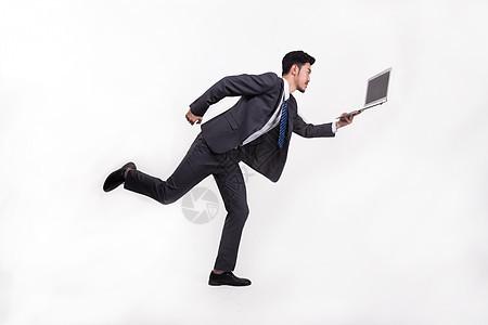 拿着笔记本电脑奔跑的上班族白领图片