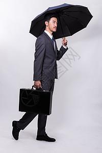 提着公文包撑伞走路的商务人士图片