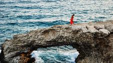 海岸岩石上穿红色长裙的女人图片
