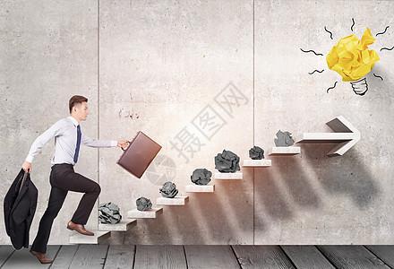 商人走向上升的楼梯与垃圾纸球图片