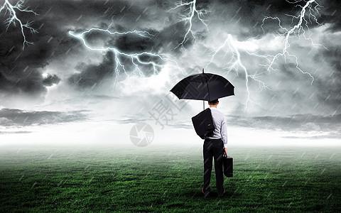 打伞商务人站在打雷下雨的草坪上图片