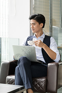 年轻商务男士落地窗前喝咖啡图片