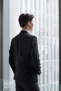 办公室落地窗前思考的商务人图片