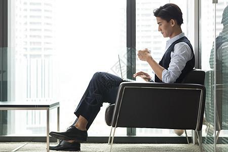 坐在落地窗前喝咖啡的商务男士图片