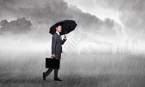 商人在暴风雨的天空下拿着一把伞图片