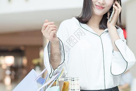 提着购物袋打电话逛街的美女图片
