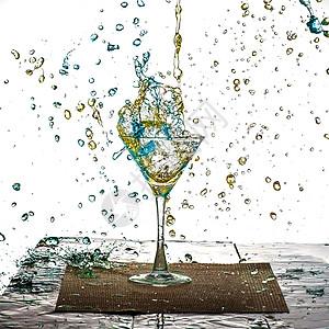 蓝色与黄色的饮料在杯中溅出水珠图片