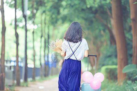 抱花女孩的走动的飘逸背影图片