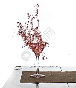 粉红色饮料溅在玻璃杯中的水珠图片