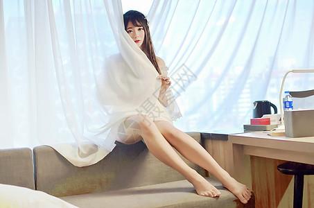 坐在窗边沙发上的年轻女性图片