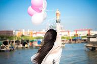 拿着气球的年轻女性背影图片