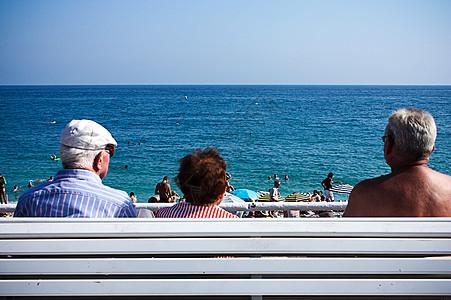 阳光下面对蓝色海洋的老人图片