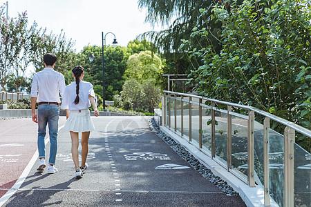 情人节情侣牵手公园散步背影图片