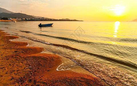 日出沙滩海浪摇小船图片