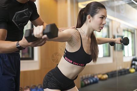 男教练在健身房给女性练习力量图片