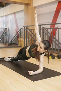 美女在健身房瑜伽垫上健身图片