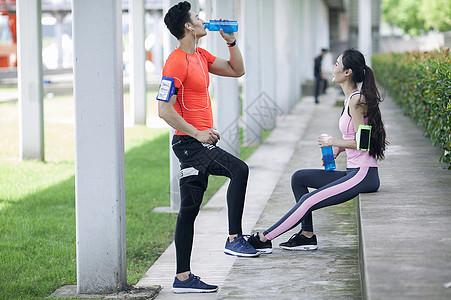 年轻男女在户外锻炼后休息喝水图片