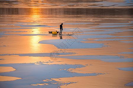 冰雪湖面上的捕鱼人图片
