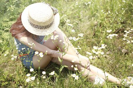 草地里坐着的戴帽子的女孩子图片
