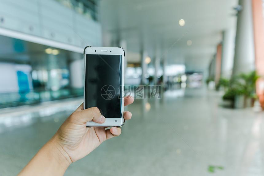 机场出行手握手机素材图片