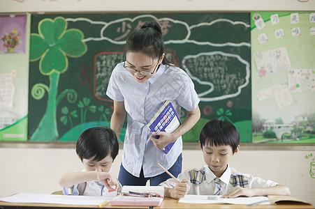 上课时老师在辅导学生认真学习图片