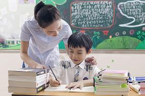 女老师在教室里给男同学辅导图片