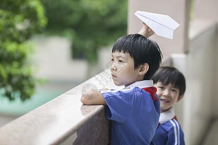 男学生在学校里折飞机玩耍图片