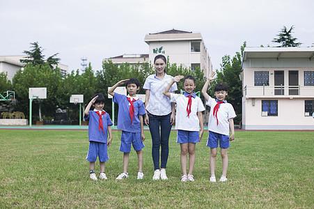 女老师和男女同学在操场上升国旗敬礼图片