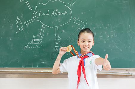 挂着奖牌竖起大拇指的小学学生图片