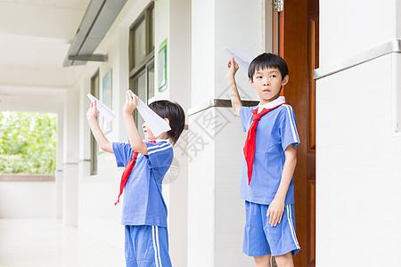 下课在走廊上玩飞机的小学生图片