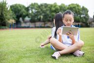 坐在草坪上使用平板电脑的小学生图片