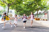 阳光下孩子们牵手快乐的奔跑图片