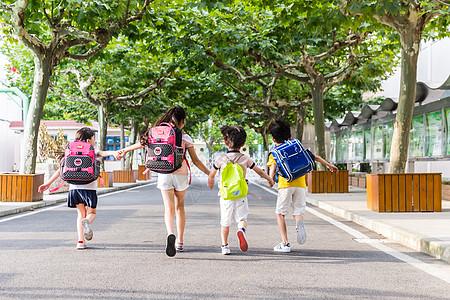 孩子们牵手快乐奔跑的背影图片